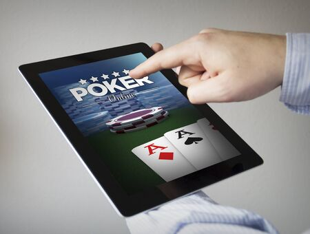 new technologies: new technologies concept: hands with touchscreen tablet with poker game on the screen. Stock Photo