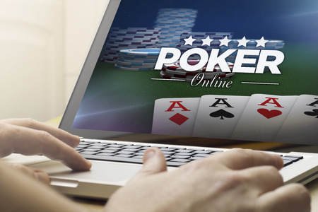 holdem: online gaming concept: man using a laptop with online poker on the screen.