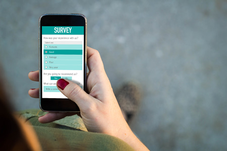 Top view of woman walking in the street using her mobile phone with online customer service satisfaction survey.