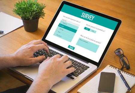 Webconcept: Man Filling Online Survey Form op een laptop.