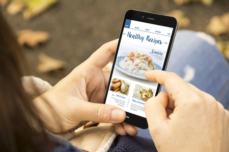 cooking concept: woman holding a 3d generated smartphone with healthy recipes blog on the screen.