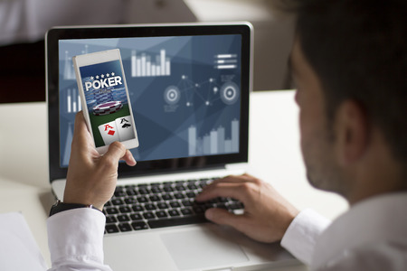 businessman distracting at work with smartphone showing poker online on screen.