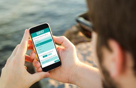 man aan de kust te vullen online klanttevredenheidsonderzoek op zijn smartphone. Stockfoto