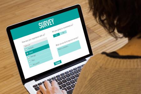 Jeune femme remplissant un formulaire d'enquête avec un ordinateur portable.