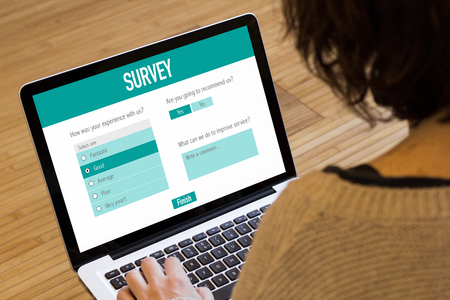 online survey: Young woman filling a survey form with laptop.