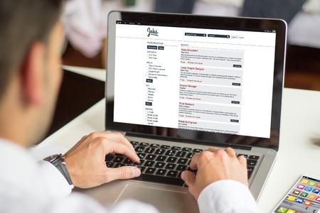 Geschäftsmann sucht nach einem Job mit einem Laptop Lizenzfreie Bilder