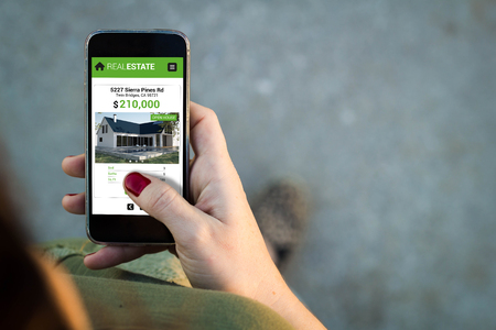 Top view of woman walking in the street using her mobile phone with real estate app.