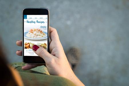 persona caminando: Vista superior de una mujer caminando en la calle utilizando su teléfono móvil para ver las recetas de vídeo con espacio de copia.