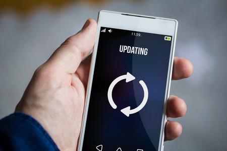 updating: man hand holding updating smartphone.