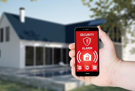 Hand houdt een telefoon met beveiligingsalarmapp op een scherm op de achtergrond van een huis.