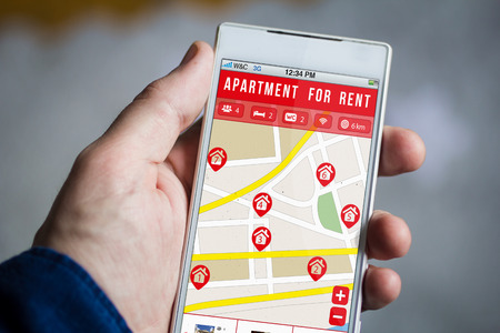 apartment for rent: man hand holding apartment for rent smartphone.