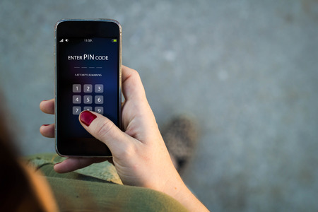 pin code: Top view of woman walking in the street using her mobile phone to enter pin code. Stock Photo