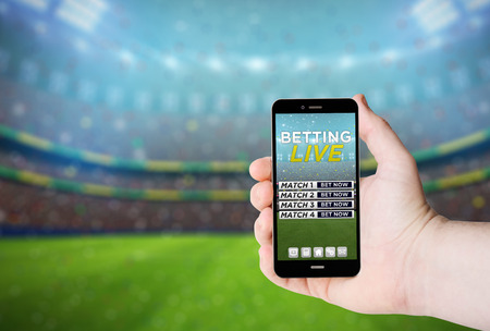 Hand hold a phone with  betting online on a screen on the background of a stadium.