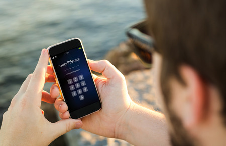 man aan de kust invoeren van pincode op zijn smartphone. Stockfoto