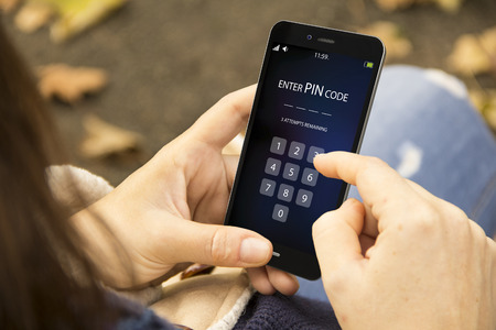 pin code: mobile security concept: woman holding a 3d generated smartphone with enter pin code interface on the screen. Stock Photo