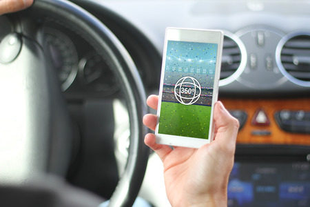 real world: lifestyle concept: Hands male with smartphone with 360 degree view stadium on the screen inside a car. All graphics on the screen are made up.