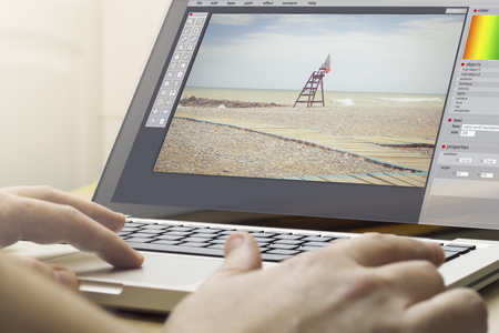 a hobby: photography concept: man using a laptop with photo editor on the screen. Screen graphics are made up.