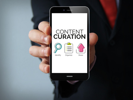 curator: Communication concept: businessman hand holding a touch phone with content curation graphic on the screen