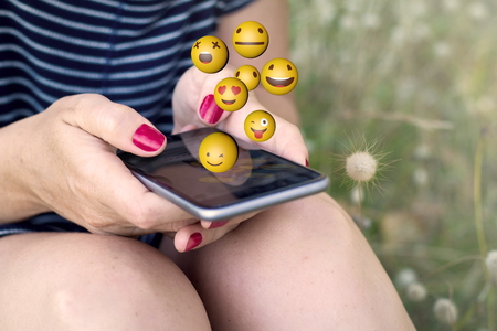 sitting woman sending emoji with smartphone on the grass. All screen graphics are made up.