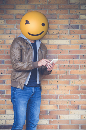 techie: technology and communications concept: man with emoji ballhead using smartphone.