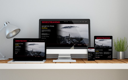 A computer, laptop, smartphone and tablet on a desktop workspace with video streaming online responsive website on screen. 3d rendering. All screen graphics are made up.