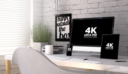 Devices mock up with 4k ultra HD resolution screen on an hardwood desk. Screen graphics are made up. Stock Photo