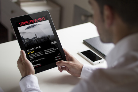bussinessman: bussinessman at office holding a tablet showing video on demand website. All screen graphics are made up.