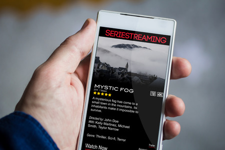 vod: man hand holding video on demand smartphone. All screen graphics are made up.