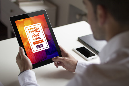 bussinessman: bussinessman at office holding a tablet exchanging a promotional code. All screen graphics are made up.