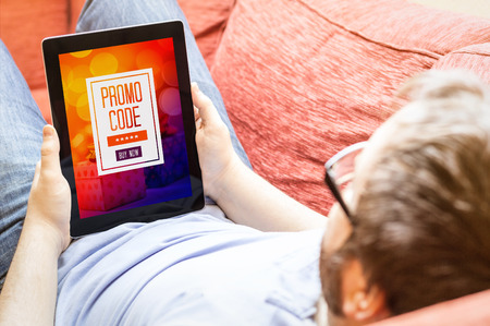 technology lifestyle concept: hipster on the sofa looking at digital promo code Stockfoto