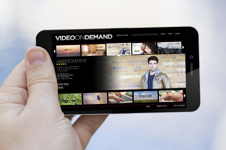 streaming: pay per view concept: hand holding an video on demand 3d generated smartphone. Screen graphics are made up. Stock Photo