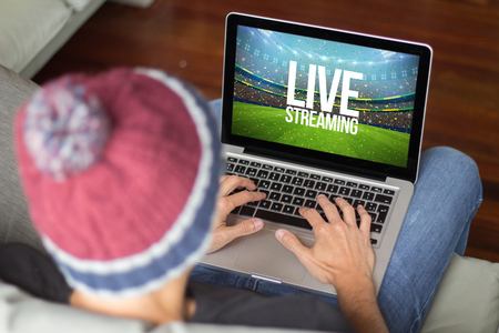 Young man watching live streaming sports event. All screen graphics are made up.