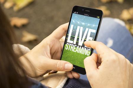 streaming de vídeo concepto: mujer con un teléfono inteligente con 3D generados por transmisión en vivo en la pantalla. Los gráficos en la pantalla se componen. Foto de archivo