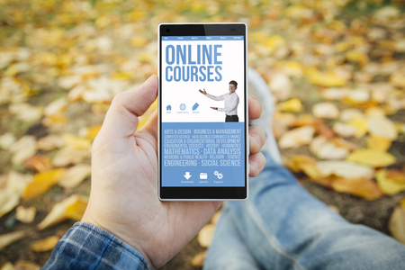 man in the park with online courses website smartphone. All screen graphics are made up.