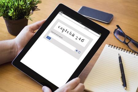 handen van een man met een captcha-apparaat over een houten werkruimtetafel. Alle schermafbeeldingen zijn samengesteld. Stockfoto