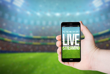 Hand hold a phone with live streaming on a screen on the background of a stadium. All screen graphics are made up.