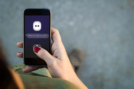 Vista superior de la mujer que camina en la calle utilizando su teléfono móvil con asistente personal inteligente. Todos los gráficos de la pantalla se componen. Foto de archivo