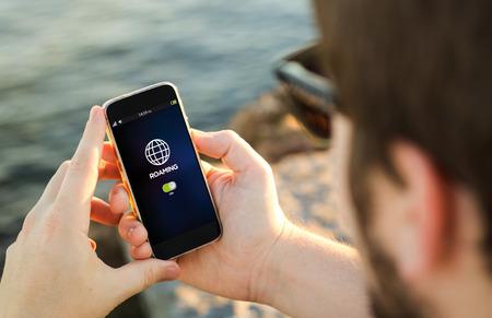 Mann an der Küste auf seinem Smartphone Überprüfung Roaming. Alle Bildschirmgrafiken bestehen. Lizenzfreie Bilder