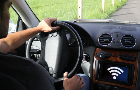 young man driving a connected car showing on-board screen computer. All screen graphics are made up.