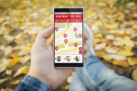 apartment for rent: man in the park with apartment for rent smartphone. All screen graphics are made up.