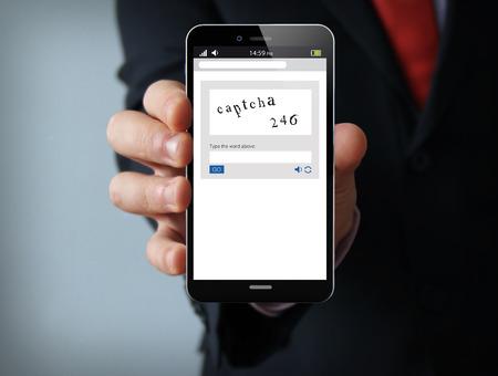 Conceito de novas tecnologias: mão de empresário segurando um telefone de toque gerado 3d com captcha na tela. Gráficos de tela são feitos. Foto de archivo - 66305131