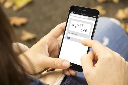 donna che tiene in mano uno smartphone generato in 3d con captcha sullo schermo. La grafica sullo schermo è composta.
