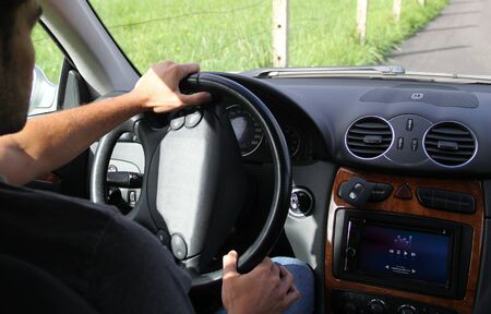 onboard: young man driving a connected car showing music on the on-board computer. All screen graphics are made up. Stock Photo