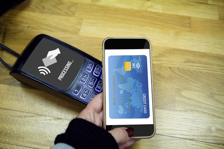 pci card: NFC Near field communication concept: Male hands using smart phone to made payment. All graphics are made up Stock Photo