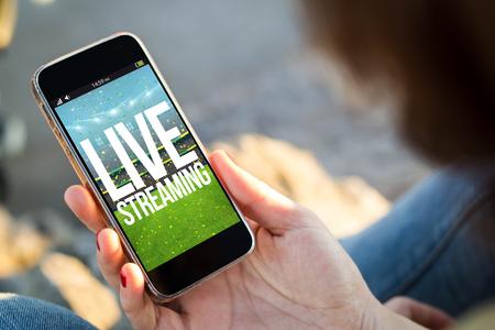 close-up beeld van een jonge vrouw met live streaming evenement op haar mobiele telefoon. Alle schermafbeeldingen zijn samengesteld.