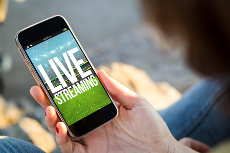 close-up view of young woman with live streaming event on her mobile phone. All screen graphics are made up.
