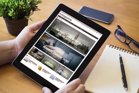 Handen van een man die een online tijdschriftapparaat over een houten werktafeltafel heeft. Alle schermafbeeldingen zijn opgebouwd.