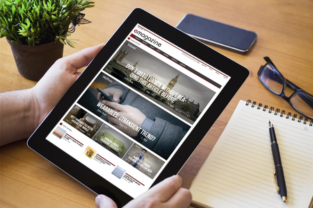 manos de un hombre que sostiene un dispositivo de revista en línea sobre una mesa de madera espacio de trabajo. Todos los gráficos de la pantalla se componen.