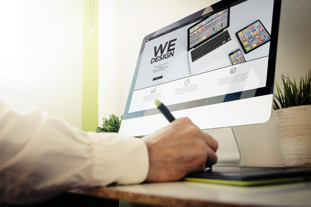 web developer designing a responsive website. All screen graphics are made up. Stock Photo