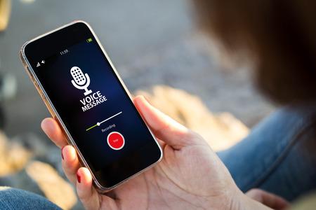通信: 携帯電話で音声メッセージを記録する若い女性をクローズ アップ。全画面表示のグラフィックスが成っています。 写真素材